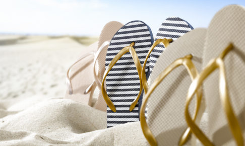 Flip flops on sand and summer time